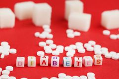 Sweetener tablets. And sugar cubes with inscription Diabetes on red background Royalty Free Stock Photos