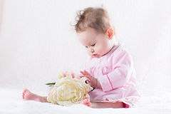 Sweetest baby girl playing with a huge white flower Stock Image
