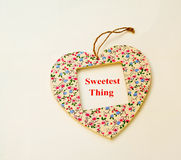 The sweetest thing. Heart shape decorated with flowers and in an open window the message in red letters ' Sweetest Thing', bright background royalty free stock photo