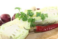 Sweetheart Cabbage with hot peppers on a board Stock Photos