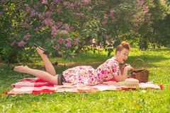 Sweetheart charming pinup girl in a summer dress on a checkered blanket in the Park near the bushes of lilac enjoys life and leisu stock photo
