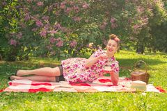 Sweetheart charming pinup girl in a summer dress on a checkered blanket in the Park near the bushes of lilac enjoys life and leisu royalty free stock photo