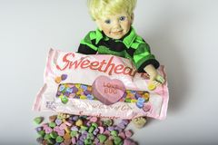 Sweethearts conversation candy hearts. Chambersburg Pa. USA 1/29/2019 child boy doll with blue eyes and blonde hair holding bag of sweethearts conversation candy stock image