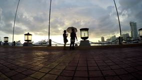 Sweethearts dating at seaside bay walk in umbrella. silhouettes. Bay walk, Manila, Philippines - July 9, 2017:  Sweethearts dating at seaside bay walk in stock footage