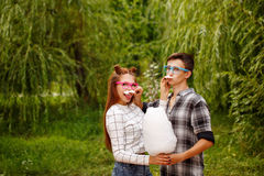 Sweethearts Teens eat sweet cotton. Sweethearts Teens eat sweet cotton and fool around. Girlfriend and boyfriend together. They wear glasses. A girl and a boy Royalty Free Stock Photo