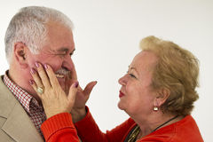 Sweetie. A senior couple laughing each other and and lady holding his face Royalty Free Stock Image