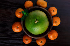 Sweetie in wooden plate with mandarines and mint leafs on dark background close-up macro Stock Photo