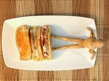 Sweetmeat and doll wooden on White plate Royalty Free Stock Photo