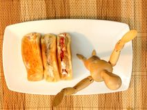 Sweetmeat and doll wooden on White plate Royalty Free Stock Image
