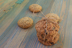 Sweetmeats. Two types of oatmeal cookies with raisins and sunflower seeds. Some tied with string to the bow, the second spread on the board. View from above Royalty Free Stock Images