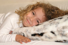 Sweetness. Little girl smiling on the couch Royalty Free Stock Photography