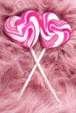 Sweetness. Two heartshaped lollipops om pink fur stock images