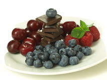 Sweets. Sweet fruits vs. sweet chocolate, isolated background Royalty Free Stock Photography