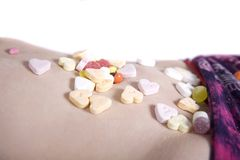 Sweets. Colorful candies on a girls body royalty free stock images