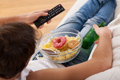 Sweets, beer and television Stock Photography