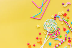 Sweets for birthday including lollipop and drops on yellow background top view copyspace Stock Photos