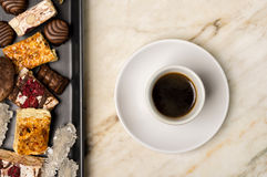 Sweets and black coffee. On a white marble table Royalty Free Stock Photography