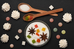 Sweets on black textured background. Marshmallows, marmalade or jelly candies, colorful dragee with anise in sugar with wooden spoons on black textured Stock Photo