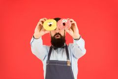 Sweets and cakes. Junk food. Hipster bearded baker hold donuts. Eat donut. Cheerful mood. Doughnut calories. Glazed royalty free stock image