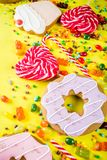 Sweets and candy creative lay out. Sweets creative lay out, dessert concept with lollipops, jellies, candy, cookies donuts and cupcakes, bright yellow background Stock Photography