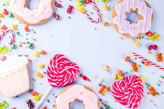Sweets and candy creative lay out. Sweets creative lay out, dessert concept with lollipops, jellies, candy, cookies donuts and cupcakes, light blue background Stock Images