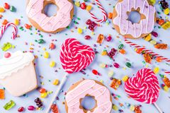 Sweets and candy creative lay out. Sweets creative lay out, dessert concept with lollipops, jellies, candy, cookies donuts and cupcakes, light blue background Royalty Free Stock Photo