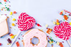 Sweets and candy creative lay out. Sweets creative lay out, dessert concept with lollipops, jellies, candy, cookies donuts and cupcakes, light blue background Royalty Free Stock Photos