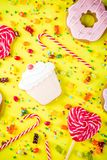 Sweets and candy creative lay out. Sweets creative lay out, dessert concept with lollipops, jellies, candy, cookies donuts and cupcakes, bright yellow background Royalty Free Stock Photos