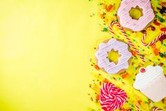 Sweets and candy creative lay out. Sweets creative lay out, dessert concept with lollipops, jellies, candy, cookies donuts and cupcakes, bright yellow background Royalty Free Stock Images