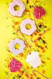 Sweets and candy creative lay out. Sweets creative lay out, dessert concept with lollipops, jellies, candy, cookies donuts and cupcakes, bright yellow background Stock Image