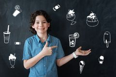 Happy boy pointing to the lemonade while being in a cafe royalty free stock image