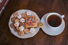 Sweets and cookies with cheerful faces and a cup of fragrant tea on a mahogany table royalty free stock photos