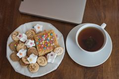 Sweets and cookies with cheerful faces, a cup of sweet tea behind the laptop on a mahogany table royalty free stock images