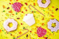 Sweets and candy creative lay out. Sweets creative lay out, dessert concept with lollipops, jellies, candy, cookies donuts and cupcakes, bright yellow background Stock Photo