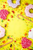 Sweets and candy creative lay out. Sweets creative lay out, dessert concept with lollipops, jellies, candy, cookies donuts and cupcakes, bright yellow background Stock Photos