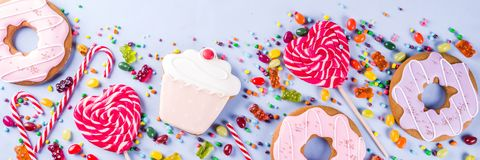 Sweets and candy creative lay out. Sweets creative lay out, dessert concept with lollipops, jellies, candy, cookies donuts and cupcakes, light blue background Royalty Free Stock Photography