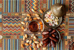 Sweets, dates and tea on a carpet. Sweets, dates and tea on a traditional Arabian carpet Stock Photos