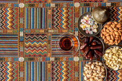 Sweets, dates and tea on a carpet. Sweets, dates and tea on a traditional Arabian carpet Stock Photo