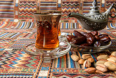 Sweets, dates and tea on a carpet. Sweets, dates and tea on a traditional Arabian carpet Stock Photography