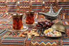 Sweets, dates and tea on a carpet. Sweets, dates and tea on a traditional Arabian carpet Stock Images