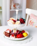Sweets and fruit plate on the kitchen. Sweets and fruit plate on the kitchen table Stock Photo