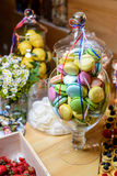 Sweets in a glass vase decorated. Sweet macaroon in a glass vase on a wooden table at a home party stock photo