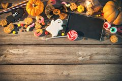 Sweets for Halloween. Trick or treat. Sweets for Halloween and fresh pumpkin on wooden table with copy space. Trick or treat royalty free stock photo