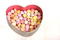 Sweets in an open silver heart shaped box. With pink inside Stock Photo