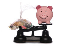 Sweets and piggybank on scales Royalty Free Stock Photos