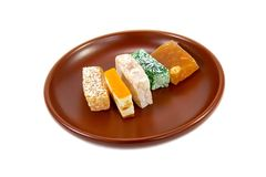 Sweets plate. Oriental sweets on brown ceramic plate isolated on white background Royalty Free Stock Photo