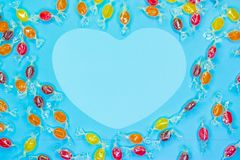 Sweets in the shape of a heart on blue background with copy space. Top view stock photography