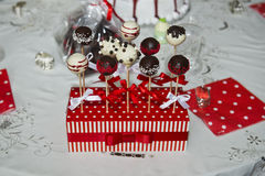 Sweets on a stick. Sweets made of dark and white chocolate on a stick in a red colored stand with ribbon Royalty Free Stock Image