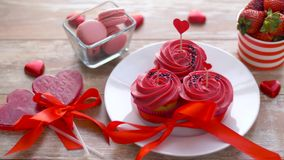 Sweets and strawberries in st valentines day. Valentines day, sweets and romantic concept - frosted cupcakes, red heart shaped candies, macarons and strawberries stock footage