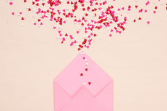 Sweets sugar candy hearts on envelope over green background Royalty Free Stock Image
